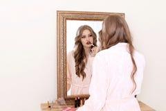 申请构成的美丽的妇女在镜子附近在化装室 库存照片