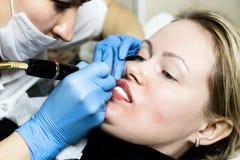 申请永久构成的美容师 有年轻美丽的妇女在她的嘴唇的化妆纹身花刺 健康温泉 免版税库存照片