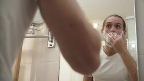 申请的人刮在面孔皮肤的泡沫和看在镜子 股票录像