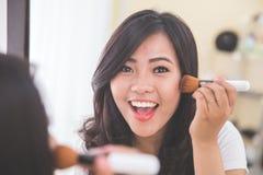 申请的妇女脸红,看镜子 免版税库存照片