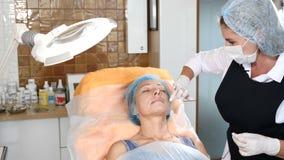 申请麻醉的美容师于一个资深女性客户 准备好的妇女秀丽治疗 4K 股票录像