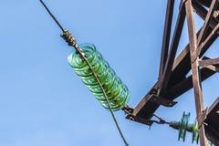 电与透明绝缘体的送电线柱子  被拍摄的特写镜头 免版税库存照片