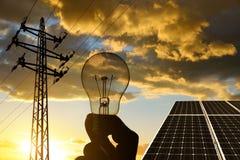 电传输定向塔、太阳电池板和手有电灯泡的反对日落 库存图片