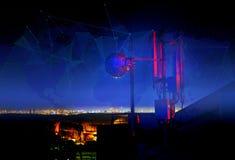 电信在晚上耸立,天线和卫星盘和城市 图库摄影