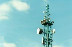 电信天线室外在有数字钟显示和蓝天背景关闭的高金属杆建筑 免版税库存照片