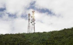 电信帆柱电视天线无线技术柱子在绿色山、蓝天和云彩小山顶的  库存照片