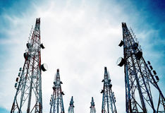 电信耸立与电视天线和卫星盘在清楚的蓝天 库存图片