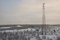 电信耸立和卫星盘在晚上天空的电信网络与日落和冬天北部森林 免版税库存图片