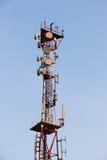 电信耸立和卫星盘在蓝天的电信网络与明亮的太阳光 免版税库存照片