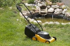 电割草机在美丽的庭院里 免版税库存照片