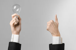 电力消费和新的企业想法题材:在拿着在灰色背景的一套黑衣服的人的手一个电灯泡在演播室 免版税图库摄影