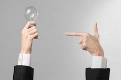 电力消费和新的企业想法题材:在拿着在灰色背景的一套黑衣服的人的手一个电灯泡在演播室 免版税库存图片