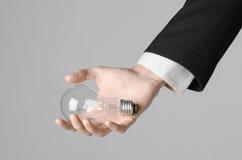 电力消费和新的企业想法题材:在拿着在灰色背景的一套黑衣服的人的手一个电灯泡在演播室 库存图片
