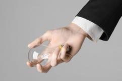 电力消费和新的企业想法题材:在拿着在灰色背景的一套黑衣服的人的手一个电灯泡在演播室 库存照片