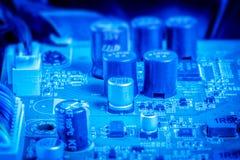 电力电容器和芯片在蓝色颜色 免版税库存图片