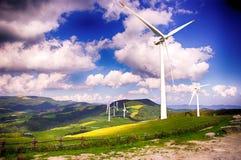 电力的风车在青山农厂和蓝天白色覆盖 免版税库存照片