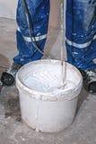 电动搅拌机混合在一个白色桶的油漆 在一个桶的叶片式拌合机墙壁、工具和辅助部件的白色油漆为 免版税库存图片