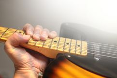 电吉他宏观摘要,弹吉他的手 免版税库存照片