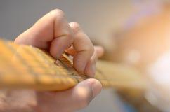 电吉他宏观摘要,弹吉他的手 免版税库存图片