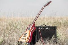 电吉他和amp在领域,音乐的概念 免版税库存照片