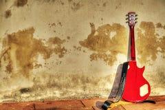 电吉他在hdr的土气墙壁倾斜了 库存照片
