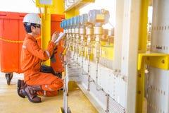 电和导航画对解决困难的技术员检查并且校准压力传送器在油和煤气平台 免版税图库摄影