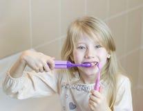 电和普通的牙刷在美丽的女孩的手上 免版税库存照片