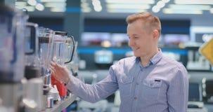 电器商店的年轻帅哥选择他的烹调的搅拌器 股票录像