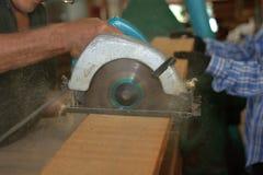 电圆锯在木匠业车间被切开一块木头工作者的againt手 图库摄影