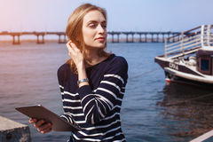 读电子书的年轻女学生在数字式片剂,当坐在内河港附近在晴天,妇女观看的录影时 免版税库存图片