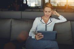 读电子书的年轻美丽的妇女通过互联网在数字式片剂,当放松在咖啡店在工作天以后时, 免版税库存图片