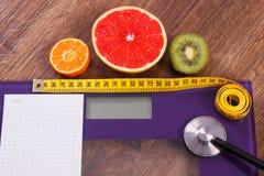 电子体重计、厘米和新鲜水果与听诊器,减肥和健康生活方式 免版税库存照片