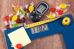 电子体重计和glucometer与测量和五颜六色的糖果,糖尿病的结果,减肥和减少吃 免版税库存图片