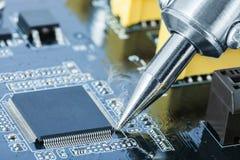 电子制造业和修理概念-焊铁接近的射击在定象微型电路的过程中 免版税库存照片