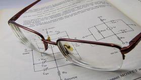 电子工程学与玻璃的书读书在开放页 免版税库存照片
