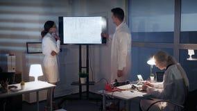 电子工程师聪明的队谈论某事在一个大电视屏幕上在实验室