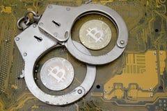 电子欺骗和黑客攻击的概念在隐藏货币区域 在闭合的钢handcu里面的两枚真正的bitcoins硬币 免版税库存照片