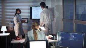 电子的多种族专家谈某事和显示在一个大电视屏幕上的在实验室