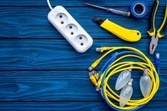电子维修服务 电灯泡,电器插座, cabel,螺丝刀,在蓝色木背景顶视图拷贝空间的堆积器 免版税库存照片