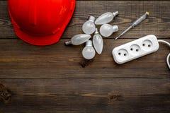 电子设施,架线工作概念 安全帽,电灯泡,在黑暗的木背景顶视图拷贝的电器插座 免版税库存图片