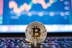 电子货币对计算机或膝上型计算机的银bitcoin有在被弄脏的背景的证券交易所桌的 Cryptocurrency骗局 免版税库存图片