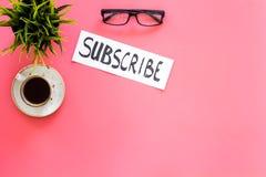 电子邮件订阅概念 递在工作书桌上的字法subcribe有植物的,玻璃,咖啡在桃红色背景上面的 库存照片