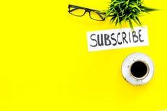 电子邮件订阅概念 递在工作书桌上的字法subcribe有植物的,玻璃,咖啡在黄色背景的 库存图片