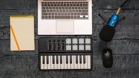 电子音乐在一张黑木桌上的搅拌器、膝上型计算机、铅笔和导线话筒 音乐演播室的设备 看法从 免版税库存图片