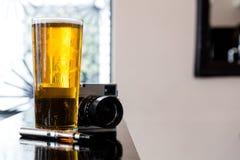 电子香烟、啤酒和照相机 免版税库存照片