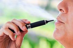 电子香烟的吸烟者与蒸汽的 免版税库存图片