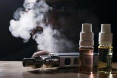 电子香烟, vaping的设备有e液体背景 库存图片