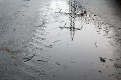 电定向塔的反射在水坑的 库存图片