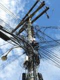 电导线和电缆迷茫的大量在电源杆 免版税库存图片