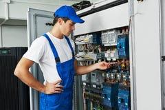 电工与在保险丝箱子的电表测试器一起使用 免版税库存图片